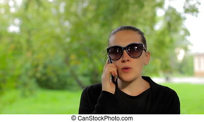 Confident young businesswoman in sunglasses speaks on the phone in green park