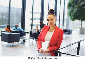 Confident young businesswoman with a laptop in office