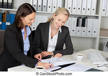 Confident Young Businesswomen Sitting At Office Desk