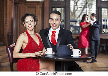 Confident Young Couple Sitting At Table While Tango Partners Dan