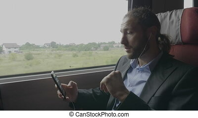 Confident young entrepreneur man traveling by train having a business video call on digital smartphone application explaining and gesturing during his trip to office work