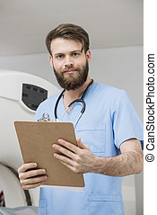 Confident Young Male Doctor With Clipboard In Examination Room