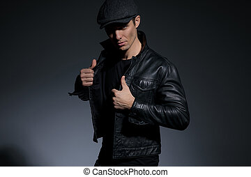 Confident young man arranging his black leather jacket
