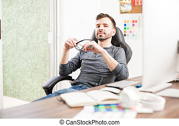 Confident young man at his office desk
