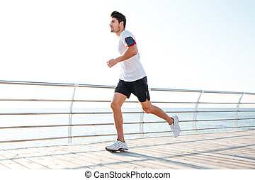 Confident young man athlete running on pier in the morning