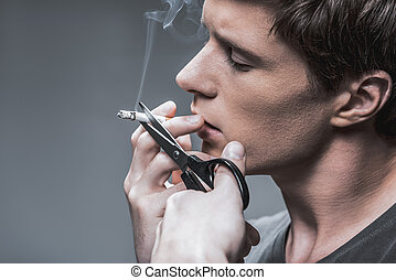 Confident young man leaving off smoking