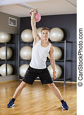 Confident Young Man Lifting Kettlebell In Gym