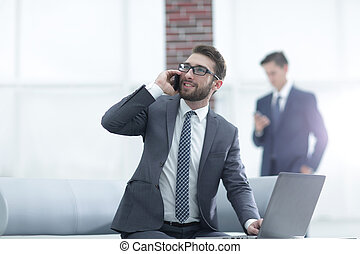 Confident young man talking on phone in office