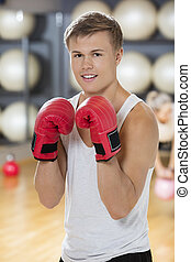 Confident Young Man Wearing Boxing Gloves In Gym