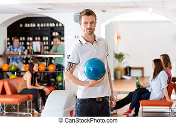 Confident Young Man With Bowling Ball in Club