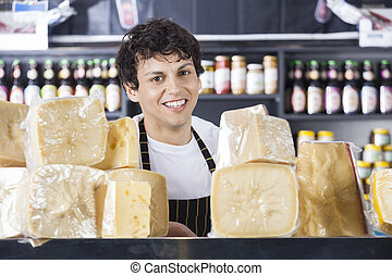 Confident Young Salesman Smiling In Cheese Shop