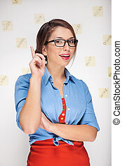 Confident young woman. Beautiful young woman gesturing and smiling while standing in front of the wall with adhesive notes on it