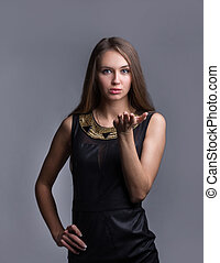 confident young woman in fashionable dress. isolated on grey