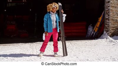 Confident young woman in snowsuit with skis