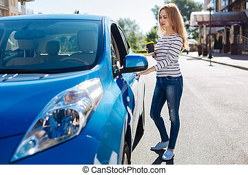 Confident young woman opening her car