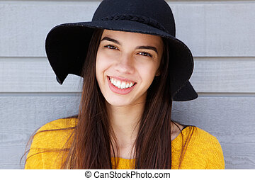 Confident young woman smiling in hat