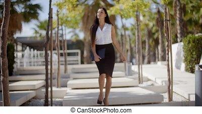 Confident young woman walking through a park