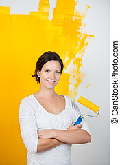 Confident young woman with a paint roller