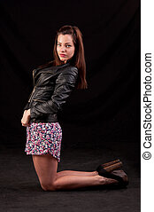 Confident young woman with leather jacket posing on her knees