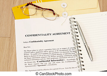 Confidentiality Agreement contract with spiral notebook and...