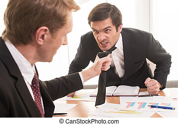 Conflict at working place. Two young men in formalwear...