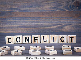 Conflict word written on wood block. Dark wood background with texture