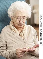 confondu, femme aînée, regarder médicament