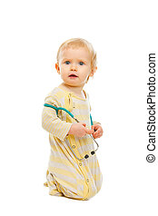 Confused baby with stethoscope sitting on floor isolated on white