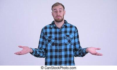 Confused bearded hipster man shrugging shoulders
