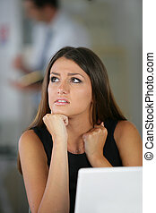 Confused brunette sat with laptop