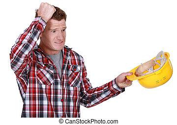 Confused builder removing hard hat