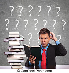 confused business man scratching his head while reading a book
