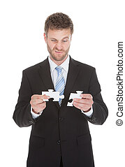 Confused Businessman Holding Puzzle Pieces