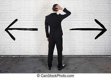 Confused Businessman Looking At Opposite Arrow Signs On Wall