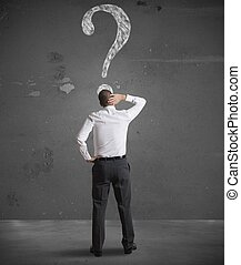 Confused businessman looking at question mark in the wall