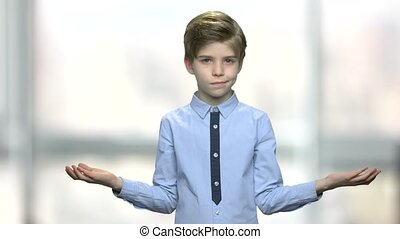 Confused caucasian boy with I do not know gesture. Portrait...