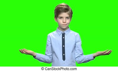 Confused child boy with i don't know gesture. Green hromakey...