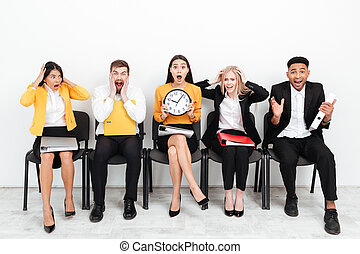 Confused colleagues sitting in office holding clock.