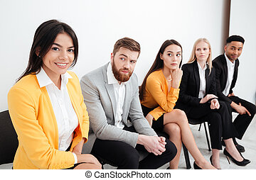 Confused colleagues sitting in office looking at cheerful woman.