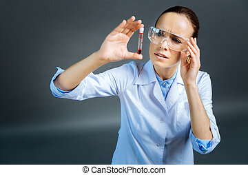 Confused female doctor looking at glass tube with blood