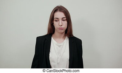 Young attractive woman with brown hair in a light t-shirt and black jacket on white background. Confused female looks ahead, does not know how to react to the situation, people's misunderstandings