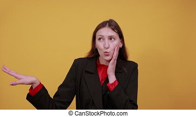 Young Attractive Brunette Woman In Black Stylish Suit, Red Shirt On Yellow Background, Confused Female Shows Direction Forefinger, Showing Guilty. The Concept Of Hangdog People