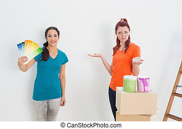 Confused friends choosing color for painting a room