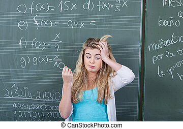 Confused Girl With Hand On Head Against Blackboard
