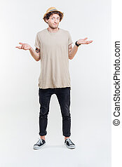 Confused handsome young man standing and shrugging