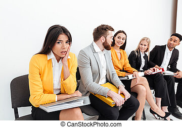 Confused lady sitting near colleagues in office