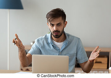Confused male worker shocked seeing warning notice at laptop