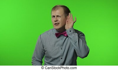 What. I can't hear you! Confused man having hearing problems, asking to say louder, difficult to listen quiet talk, misunderstanding in communication. Portrait of guy posing on chroma key background
