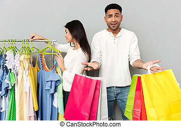Confused man holding shopping bags while woman choosing clothes
