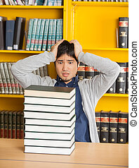 Confused Man Looking At Stacked Books In Library
